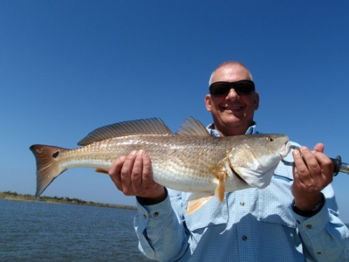 Bill Seals with another nice Redfish. Photo by: Dennis Burns