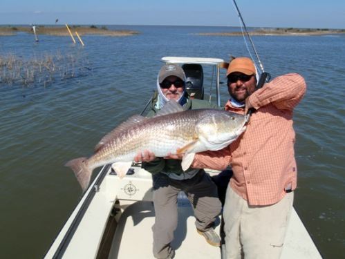 Captain Bryan Carter holds Dennis' big fish on the boga. Photo by: Bill Seals